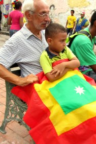 A grandfather and his grandson sit with a Cartagena flag.