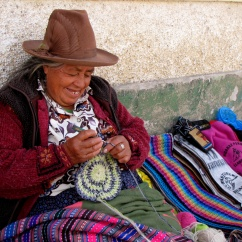 Huaraz resident knitting and selling scarves and hat.