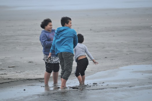 Siblings play at the beach on a windy day in Ōhope, Bay of Plenty, New Zealand.