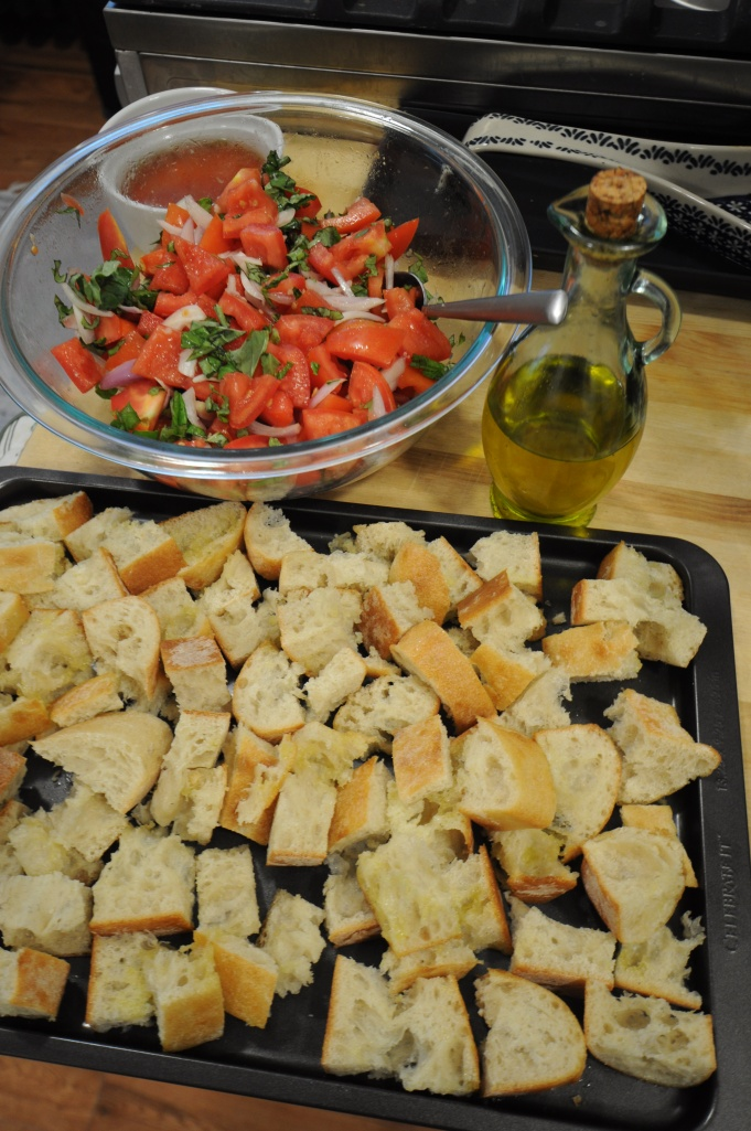 Cut Italian bread and a tomato salad prepared to make panzanella.
