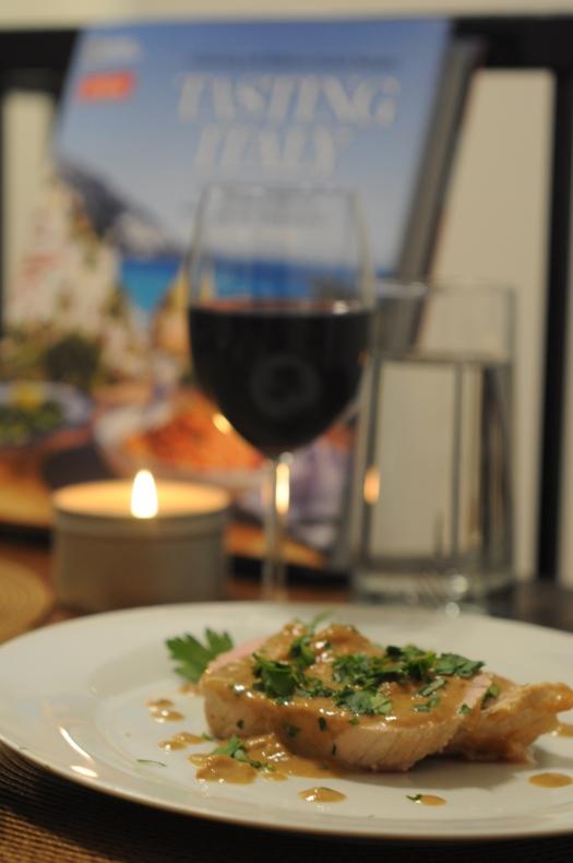 A meal of Milk-braised pork roast (arrosto di maiale al latte) with wine.